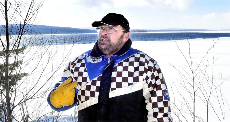 Rangeley resident Tim Lyons stands beside Rangeley Lake Tuesday near an expanding section of open water. Five years ago, Lyons' sled broke through the ice on Rangeley Lake, but he quickly scrambled out of the water. He was lucky, but it was a painful experience, he said.