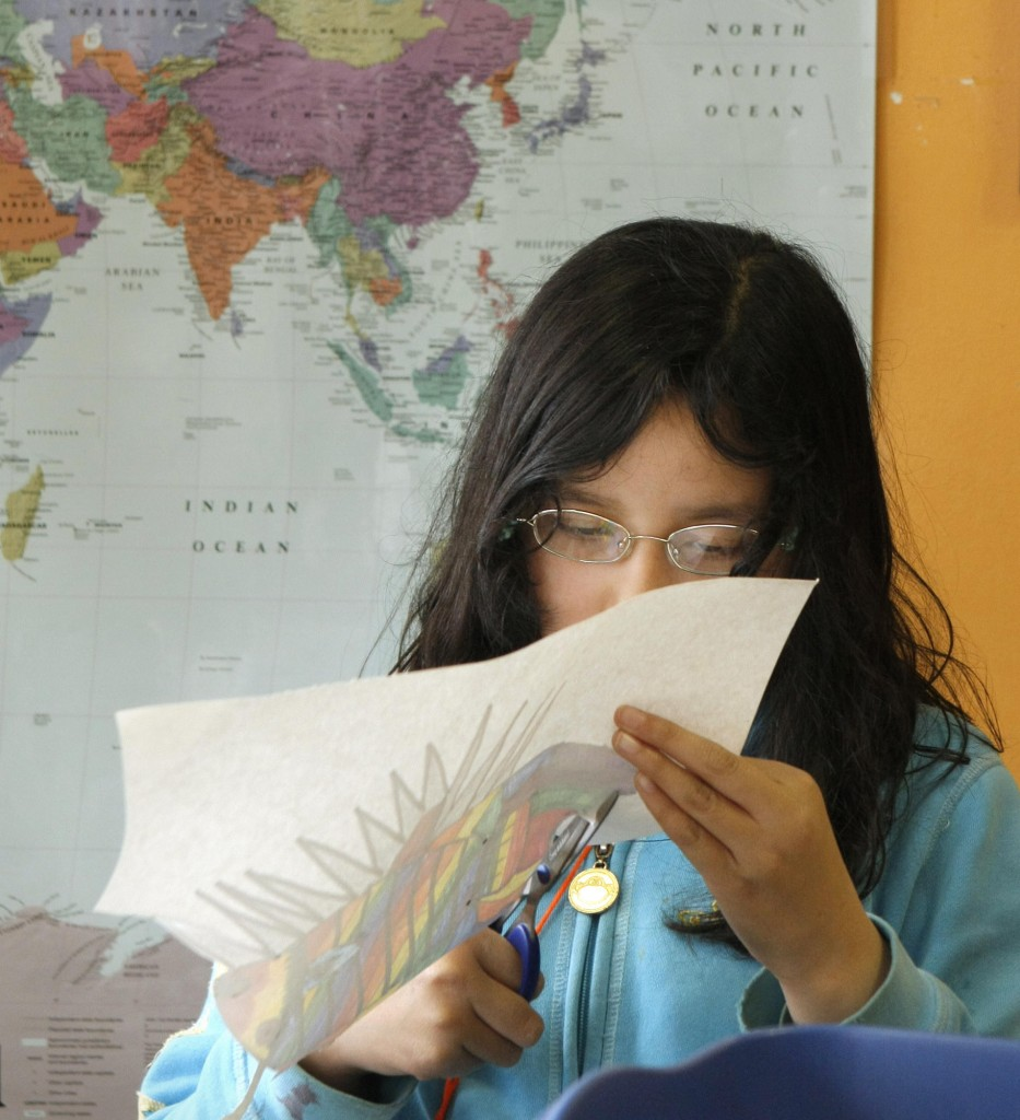 Carol Hong, a fourth grader at Reiche School, cuts out a drawing of a fish during an after school program at LearningWorks in Portland's West End in this May 6, 2009 file photo.