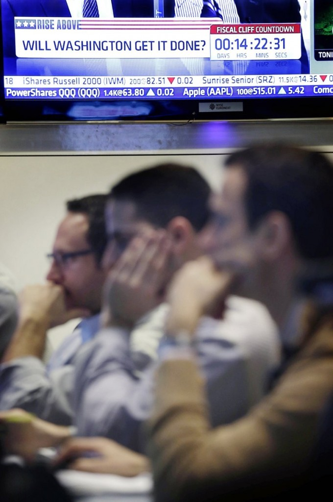 "A TV news show reports on the ""fiscal cliff"" above traders in New York on Monday."