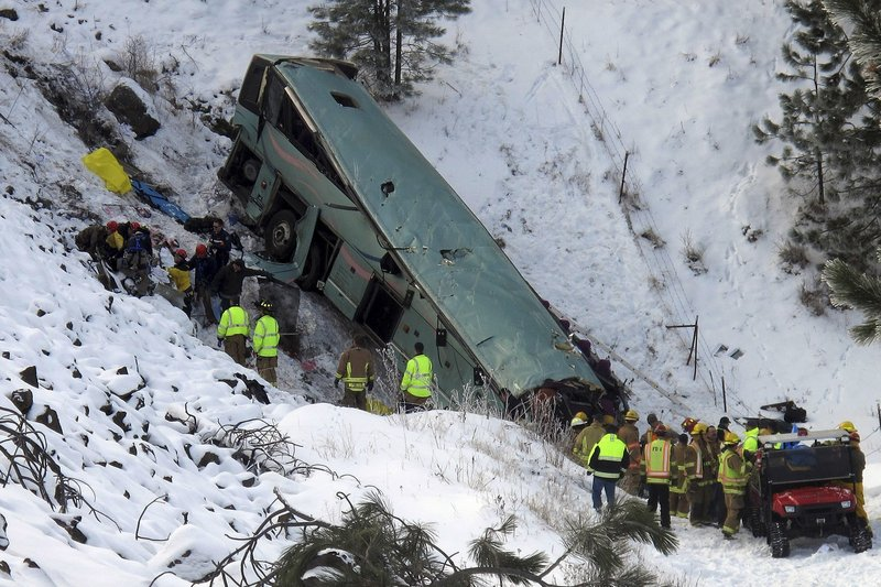 Emergency personnel respond to the scene of a multiple-fatality accident after a tour bus careened through a guardrail along an icy highway and fell several hundred feet down a steep embankment Sunday about 15 miles east of Pendleton, Ore.