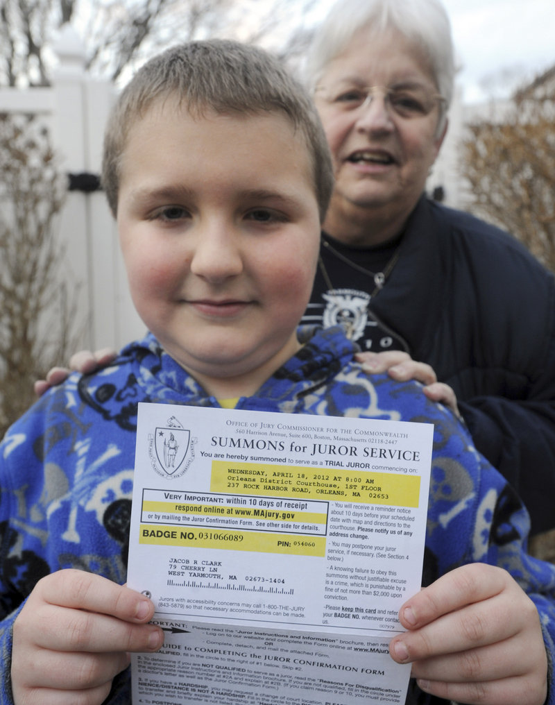 Jacob Clark, 9, displays the notice he received to appear for jury duty in South Yarmouth, Mass., in March. His grandmother Deborah Clark stands behind him. Documents mistakenly listed 1982 for his birth year instead of 2002.
