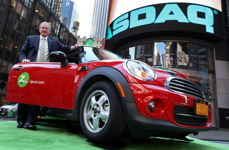 Zipcar Chairman and CEO Scott Griffith stands with a Zipcar Mini-Cooper before the opening bell outside the NASDAQ market site in New York. Avis is buying Zipcar for $491.2 million, expanding its offerings to hourly rentals.