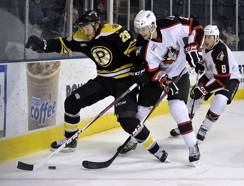 Providence's Christian Hanson, 26, tries to maintain control of the puck along the boards behind the Pirates' goal while David Rundblad, 2, and Ethan Werek, 8, move in during Wednesday night's game in Portland.