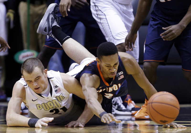 lIllinois guard Joseph Bertrand, right, and Purdue forward D.J. Byrd dive for a loose ball in first-half action of Wednesday's game in West Lafayette, Ind.