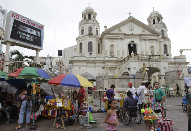 """No to abortion"" flashes on an electric sign outside the Minor Basilica of the Black Nazarene in Manila on Thursday. Catholic leaders consider the new law that provides state funding for contraceptives an attack on the church's core values."