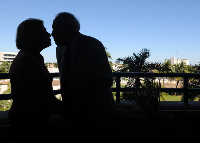 Zelda Luxenberg, left, and Robert Levinson share a kiss on the balcony of Robert's condo in Delray Beach, Fla. The two paid $1,000 to see their love story in print.