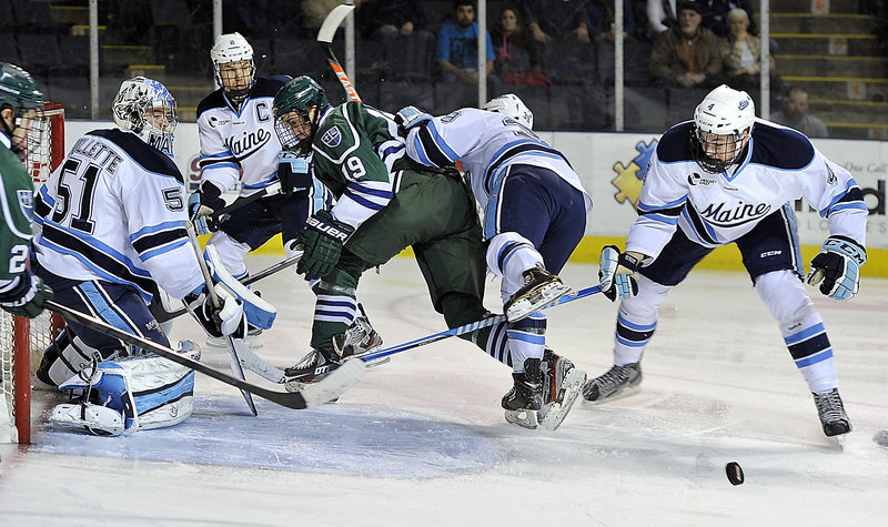 Maine goalie Martin Ouellette keeps his eye on the loose puck as Mercyhurst's Matthew Zay (19) is knocked out of the play by Maine's Joey Diamond during a 2-1 win by the Black Bears at the Cumberland County Civic Center on Friday night.
