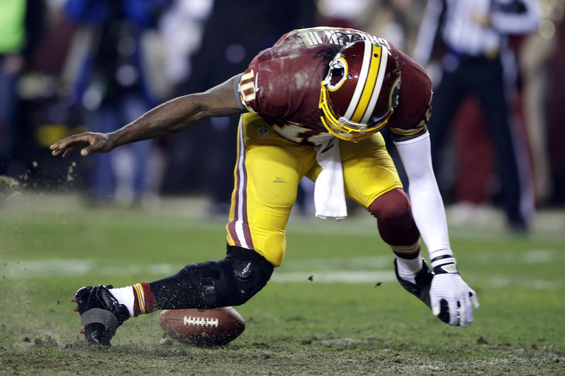 Robert Griffin III's right leg bends awkwardly as he tries to scoop up an errant snap in the fourth quarter. Griffin left the game and didn't return.