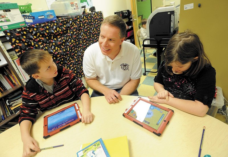 Chris Rhoda, center, a member of Watch D.O.G.S., a group of fathers who volunteer at Belgrade Central School, sits with students Brandon Denardo, 8, and Isabell Frost, 9. The national volunteer group was created to provide more of a male presence in schools.