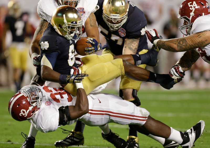 C.J. Mosley, 32, of Alabama takes down Notre Dame's Theo Riddick in the first half of Monday night's BCS championship game in Miami. The Crimson Tide won their second straight BCS title and third in four years, 42-14.