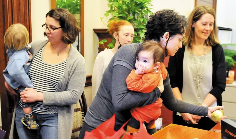 Lilijana Cvetkoska, center, of Cape Elizabeth clutches her infant daughter, Olga Malenko, while demonstrating at the governor's office for a ban on BPA in baby food packaging.