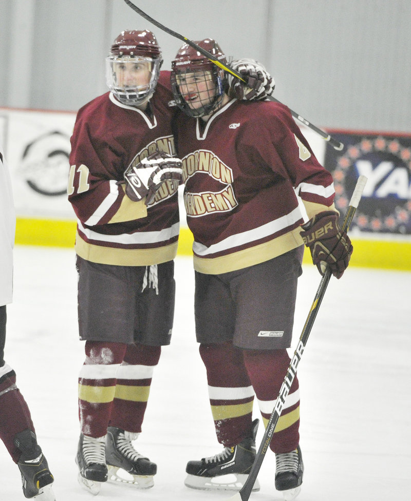 Owen Elliott, right, celebrates with Justin Cloutier after scoring a goal in the first period. Cloutier later added an empty-net goal to clinch the victory.