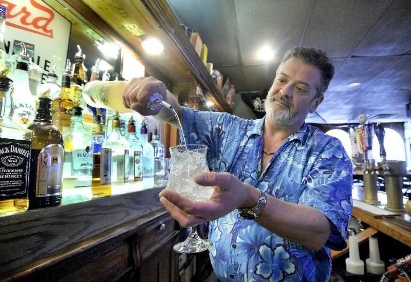 Bartender Doug Johnson pours a mango rum on the rocks at Pizza Villa in Portland.