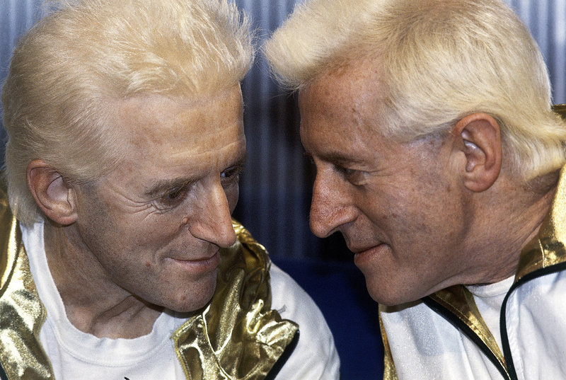 Jimmy Savile, right, who died last year at age 84, poses with a wax model of himself at Madame Tussauds museum in London in 1986. A police investigation has revealed how he used his celebrity status to prey on young, vulnerable people – including those at schools and hospitals.
