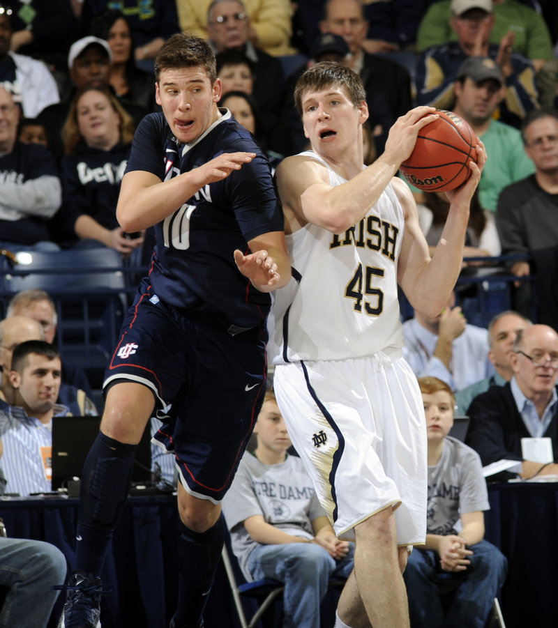 Notre Dame's Jack Cooley grabs a rebound away from Connecticut's Tyler Olander during Saturday's game at South Bend, Ind. UConn upset the 17th-ranked Fighting Irish, 65-58.