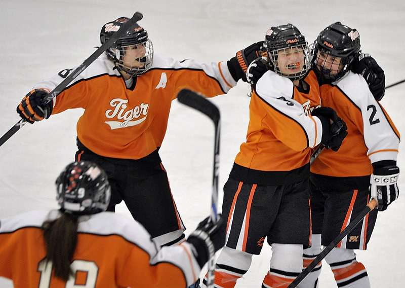 Celebrating a goal for Biddeford are assistant captain Dalani Roy, left, along with Brea Rivard hugging Abbie Paquette, right.