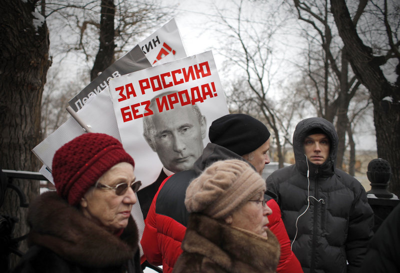 "A poster of Russian President Vladimir Putin with the words ""For a Russia without Herod!"" is seen Sunday at a Moscow rally against a law barring Americans from adopting Russian children. The biblical ruler Herod ordered the massacre of infants in Bethlehem at the time of Jesus."