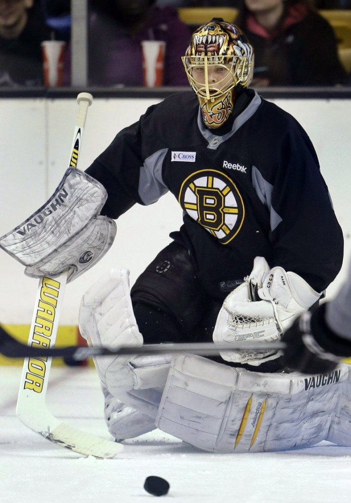Bruins goaltender Tuukka Rask keeps his eye on the puck during practice at the TD Garden on Sunday as Boston opened its abbreviated training camp.
