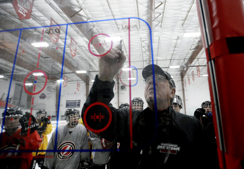"Scarborough High School boys' hockey coach Norm Gagne, 66, and now in his 38th year as a coach, draws up plays during a practice at MHG Ice in Saco. On coaching, he said: ""It blows my mind to see how much it's changed."""