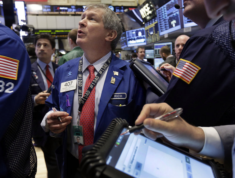 Trader Richard Newman checks prices as he works on the floor of the New York Stock Exchange. The markets edged mostly lower Monday.