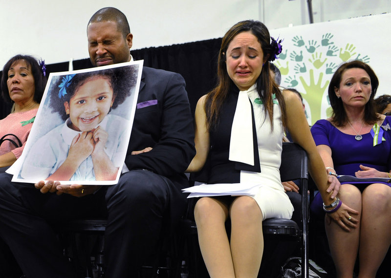 Jimmy Greene, foreground left, Nelba Marquez-Greene, center, parents of Sandy Hook shooting victim Ana Marquez-Greene, and Nicole Hockley, right, mother of victim Dylan Hockley, react during a Monday news conference in Newtown, Conn.
