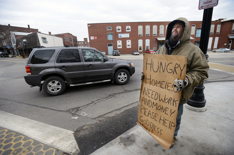 Mark Crowley of Saco panhandles for money at the corner of Alfred and Main streets in Biddeford. Crowley says he is an unemployed carpenter who is currently living in a tent in the woods in Saco as he tries to find a job.
