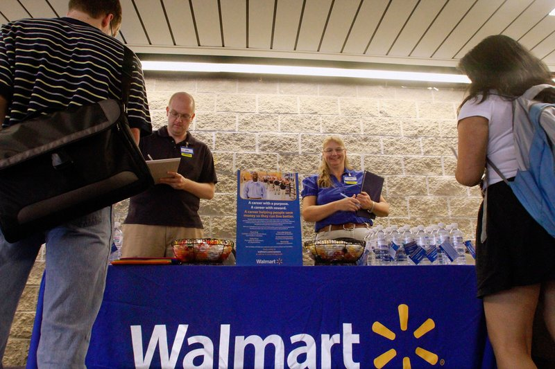 Walmart employees Jon Christians and Lori Harris take applications during a job fair at the University of Illinois Springfield campus. The nation's largest private employer pledged Tuesday to hire more than 100,000 veterans.