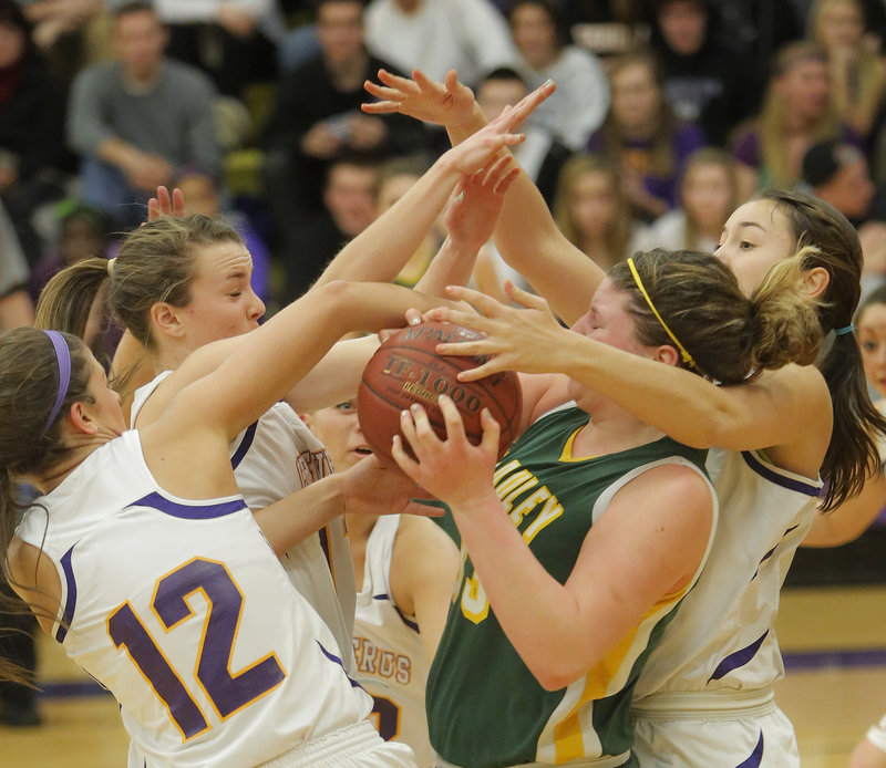 Victoria Lux of McAuley controls the ball Tuesday night among Cheverus defenders, including Jill Libby, 12, and Jess Willerson, right. McAuley won, 51-30.