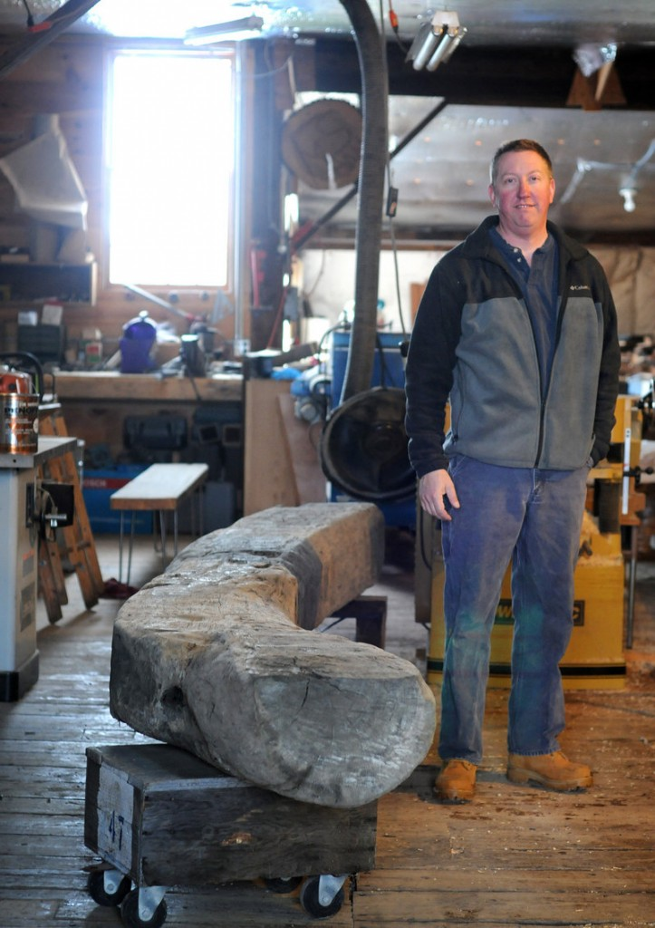 In this Jan. 4, 2013 photo, Tom Mann, of T.S. Mann Lumber, stands near a 300 year old oak beam at his shop in Athol, Mass. The beam was dug up near Boston Harbor where the Spaulding Rehab Center is being built. Mann has been commissioned to create a bench for the center. (AP Photo/Worcester Telegram & Gazette, Tom Rettig)