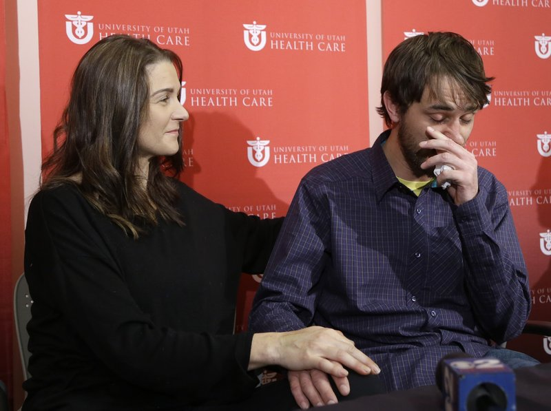 Elisabeth Malloy comforts her boyfriend, Adam Morrey, as he talks about their ordeal, at a news conference Wednesday at University Hospital in Salt Lake City.