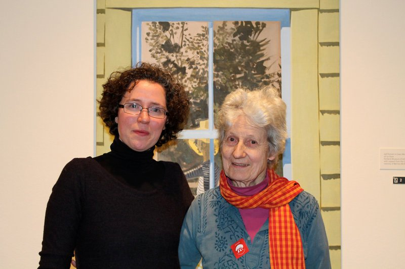 "Jessica May, curator of contemporary and modern art at the Portland Museum of Art, with artist Lois Dodd, standing before her painting, ""Self-Portrait in Green Window, 1971."""