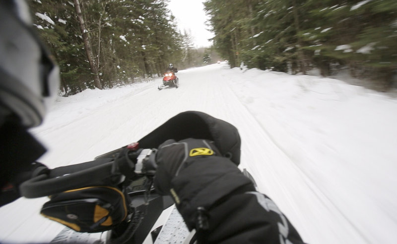 Ryan Harvey of Sanford drives his snowmobile about 45 mph, while staff photographer Gregory Rec rides on the back, holding his camera out to the side with one hand and holding onto Harvey with the other hand. Harvey said that the culture of snowmobiling in Maine, with dozens of clubs teaching safe riding habits, makes riders feel safe.