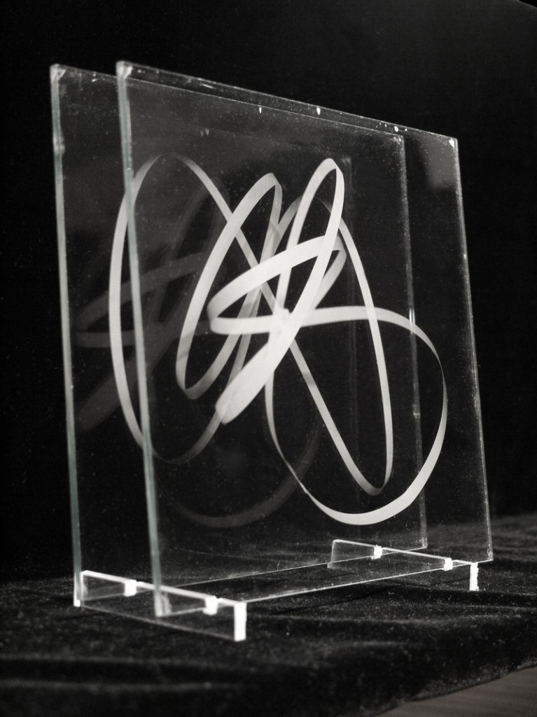 """itiswhatitis"" features two series of works by Michael Kolster, including one involving glass plates and swirls of ribbon."
