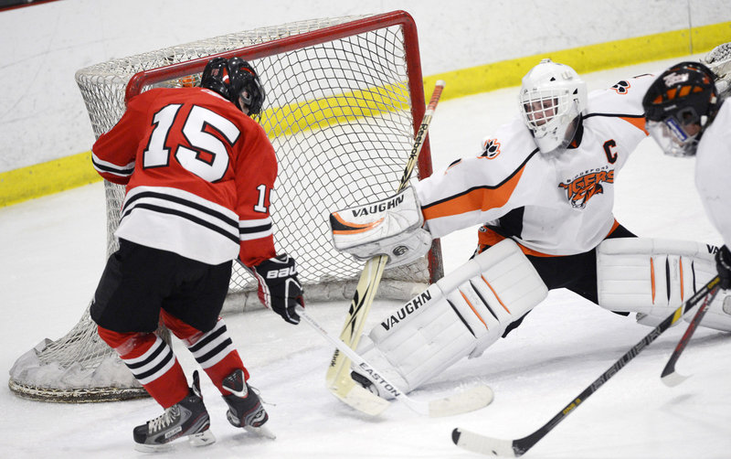 Biddeford goalie Jon Fields, who finished with 25 saves, stretches to deny a scoring bid, blocking a shot by Cam Brochu of Scarborough.