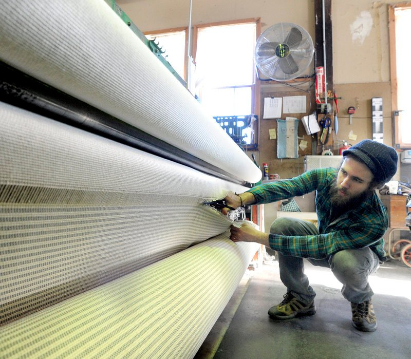 Ryan Benoit cuts a roll of fabric from a loom at the Brahms Mount blanket factory.