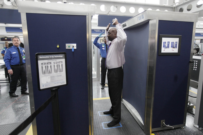 Volunteers pass through the first full body scanner installed at O'Hare International Airport in Chicago. The airport scanners with their all-too-revealing body images will soon be going away because the company that makes them can't fix the privacy issues.