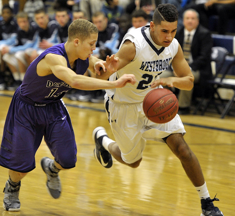 Keenan Lowe of Westbrook controls the basketball while attempting to hold off Deering guard Dominic Lauture.