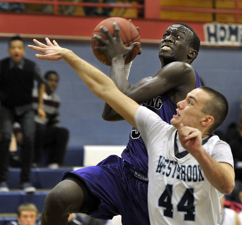 Labson Abwoch, who scored 18 points Friday night for Deering, heads to the basket against Noah Collins of Westbrook during visiting Deering's 49-41 victory.