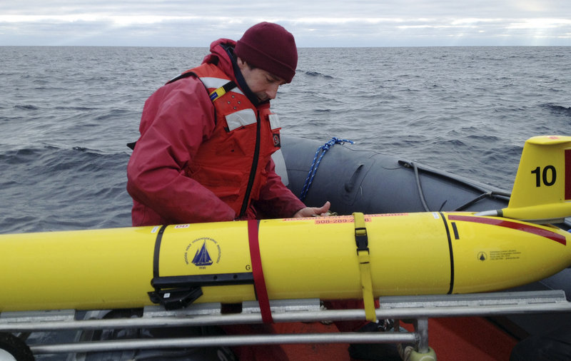 Aboard a ship Dec. 4 in the Gulf of Maine, Mark Baumgartner, a scientist at Woods Hole Oceanographic Institution and project co-leader, secures an underwater robot, or glider, used to collect acoustic data to help scientists locate endangered whales.