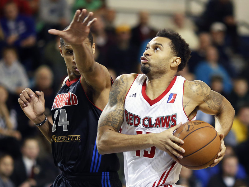 Maine's Xavier Silas drives past Springfield's Carleton Scott in the Red Claws' 106-92 win Monday at Portland. Silas, one of six Red Claws in double figures, had 13 points.