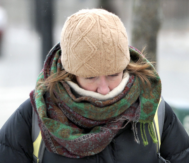 Holly Hurd-Forsyth from Peaks Island keeps her head down against the cold wind as she walks to work Tuesday, Jan. 22, 2013.