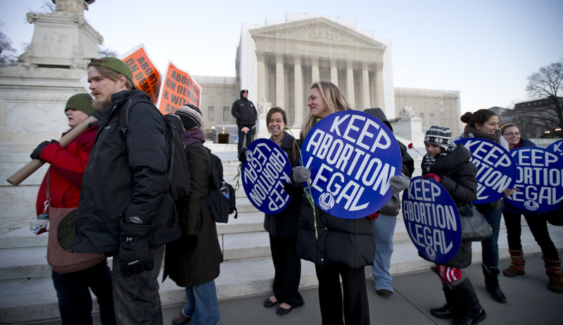 Bettina Hager, center, and Jeff Foster, left, join a candlelight vigil Tuesday in front of the U.S. Supreme Court to commemorate the 40th anniversary of Roe v. Wade.