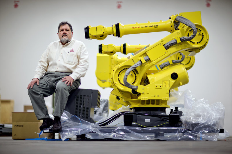 n this Jan. 15, 2013, photo, Rosser Pryor, Co-owner and President of Factory Automation Systems, sits next to a new high-performance industrial robot at the company's Atlanta facility. Pryor, who cut 40 of 100 workers since the recession, says while the company is making more money now and could hire ten people, it is holding back in favor of investing in automation and software. (AP Photo/David Goldman)