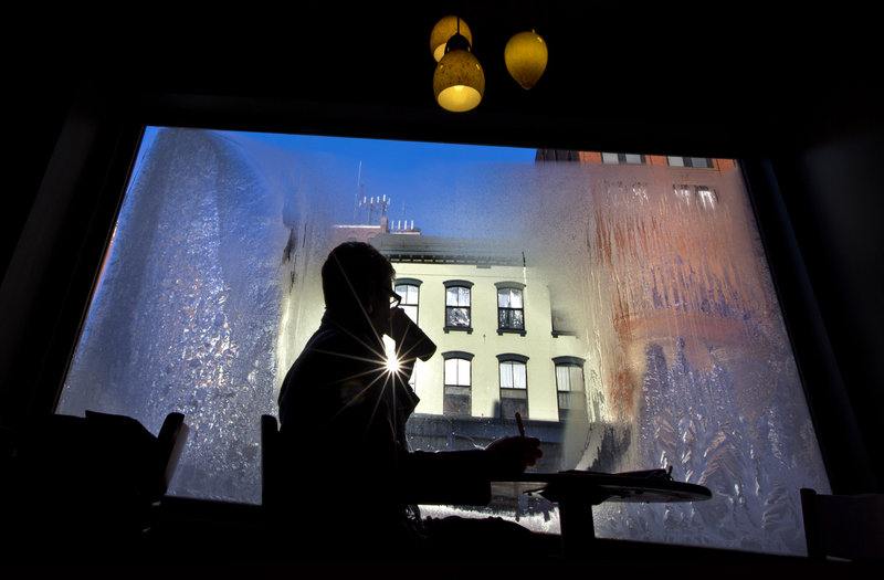 Erin Leighton sips a coffee while seated next to a frost-covered window at a coffee shop, Thursday, Jan. 24, 2013, in Portland, Maine. An arctic cold front with sub-zero temperatures continues to grip the region. (AP Photo/Robert F. Bukaty)