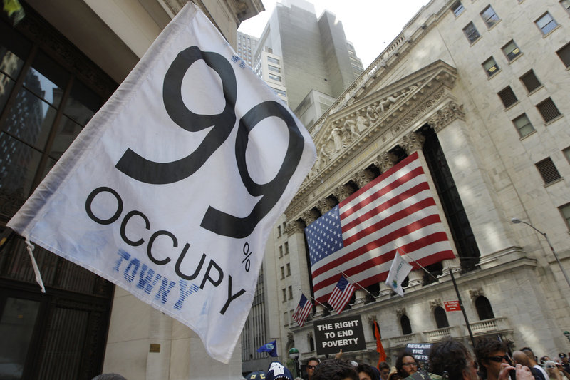 "Occupy Wall Street protesters walk past the New York Stock Exchange last July 11. The real threat to ""our American way of life"" isn't socialism, but ""the concentration of power in a small group of people at the very top of the social pyramid,"" like executives who get bonuses when their companies are restructured and many workers laid off, a reader says."