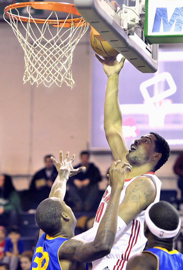 Maine's Fab Melo scores two of his only four points while Mickell Gladness tries to defend.