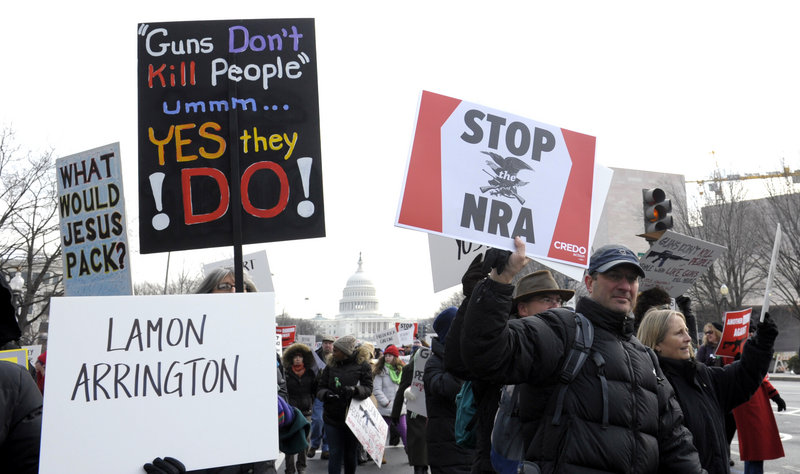 Marchers supporting gun control walk from the U.S. Capitol down the Mall in Washington on Saturday. Some signs, like the one at lower left, bore names of victims of gun violence.