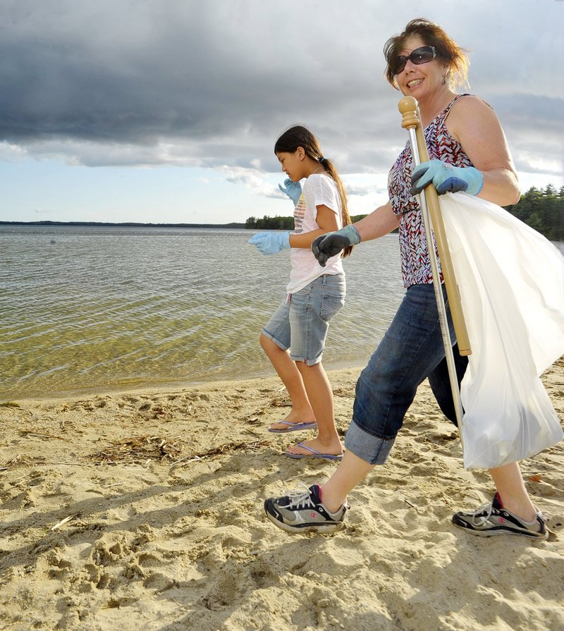 Joanne Alfiero and her daughter Grace pick up trash on Raymond Beach last May, when Alfiero was the beach manager. She says the town needs a full-time manager in summer, which she is unable to do.