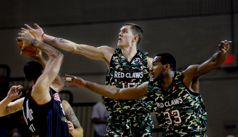 Micah Downs, center, and Chris Wright of the Red Claws play tight defense against Springfield's Carleton Scott during Maine's 120-112 win Sunday at the Portland Expo. The Red Claws wore special uniforms for Military Appreciation Day.