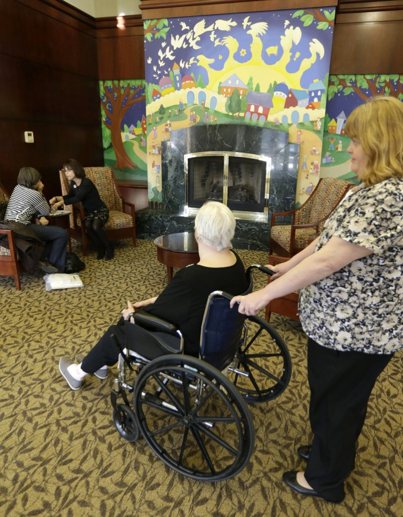 Caregiver Kim Bauer navigates an elderly woman's wheelchair at the Cedar Village retirement community in Mason, Ohio. The woman, who is in her 70s, was allegedly abused by a relative. Cases of elder abuse typically go undetected, experts say, because the abuse – often by family members – is not reported due to embarrassment or fear.